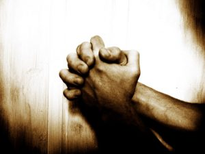 Clasped hands in pleading prayer