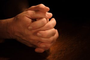 Hands clasp in prayer