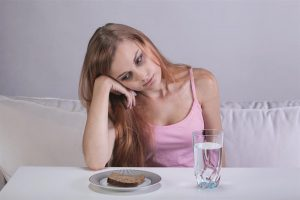 Young lady liking sadly at a small slice of bread and glass of water
