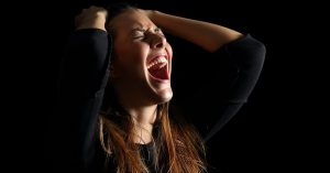 Woman with mouth open wide, eyes tight shut, hands gripping the top of her head. She looks in agony, crying out to God.