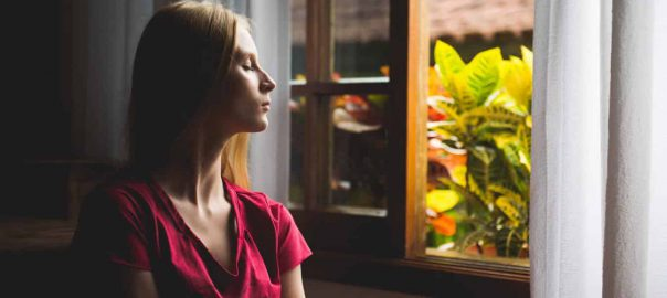 Woman looking out the window calmly