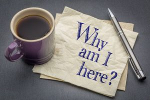 "Cup of coffee and a pen on a pile of papers with the question ""Why am I here""."