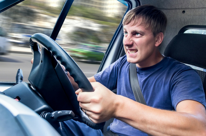 Man gripping steering wheel and gritting his teeth as trees outside whoosh past