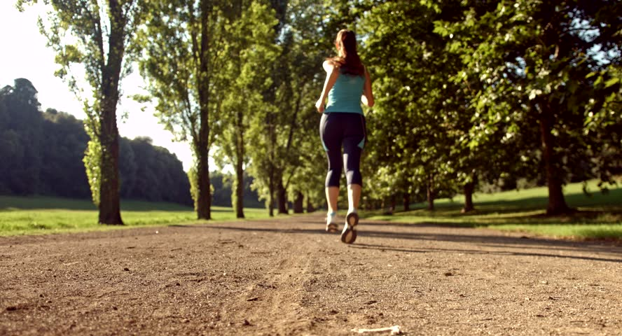 Female running down a track between a line of trees
