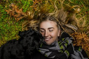 Person lying on the ground smiling broadly with a dog by their side