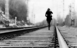 Lady walking on her own down a railway track