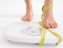 Stepping on bathroom scale with tape measure