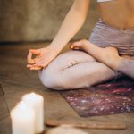 Woman in yoga pose with candles
