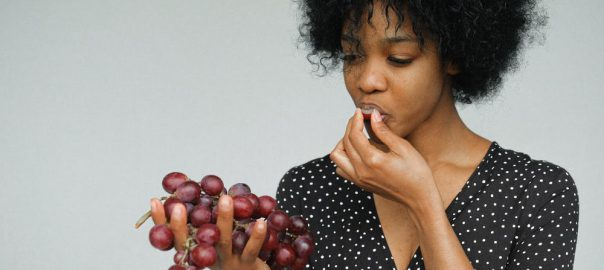 Lady eating grapes