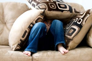 Child hiding under cushions on the sofa
