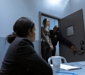 Female in police station in handcuffs with police officers
