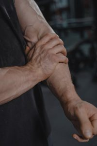 male holding arm muscle in pain