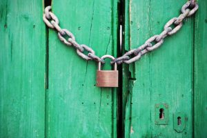 green wooden door with chain and padlock