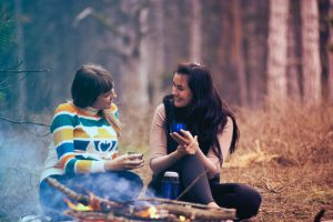 2 people chatting by a fire in a wooded area