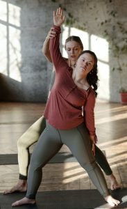 2 women, 1 with Down syndrome, doing yoga together