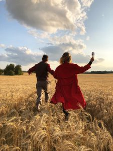 man and women running in corn field holding hands. carefree