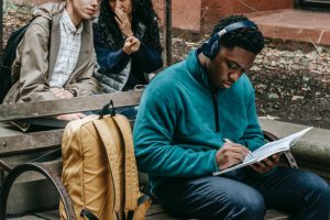 Black man sitting with headphones on writing in a book with 2 people whispering behind him