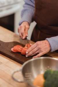 close up of hands chopping tomato