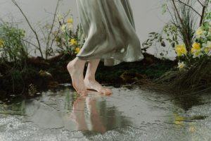 woman in grey skirt and bear feet dancing in puddle