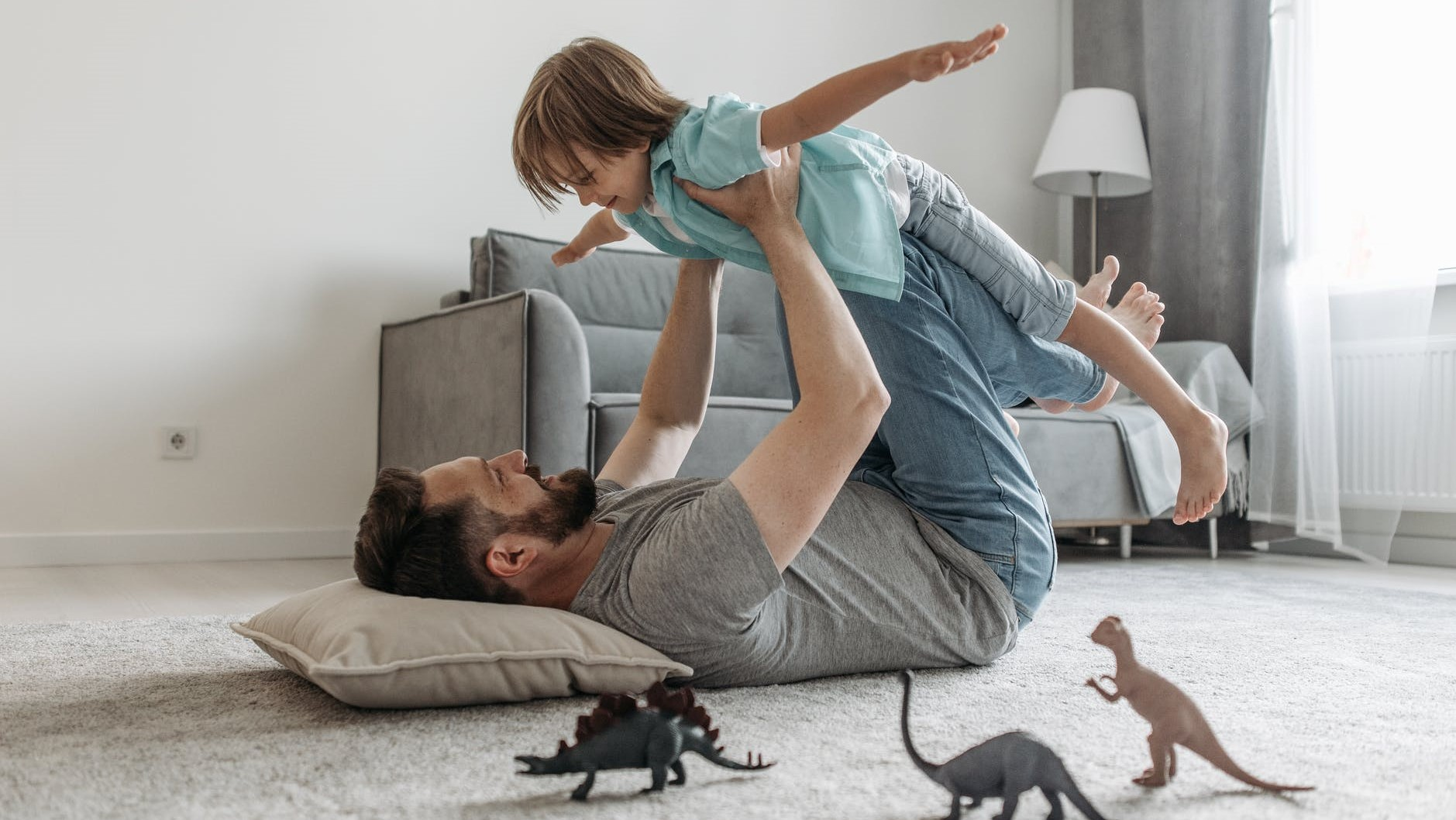 father lying on the floor holding his son above him with his arms out playing aeroplane
