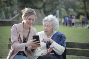 young female sharing something on her phone with an older female